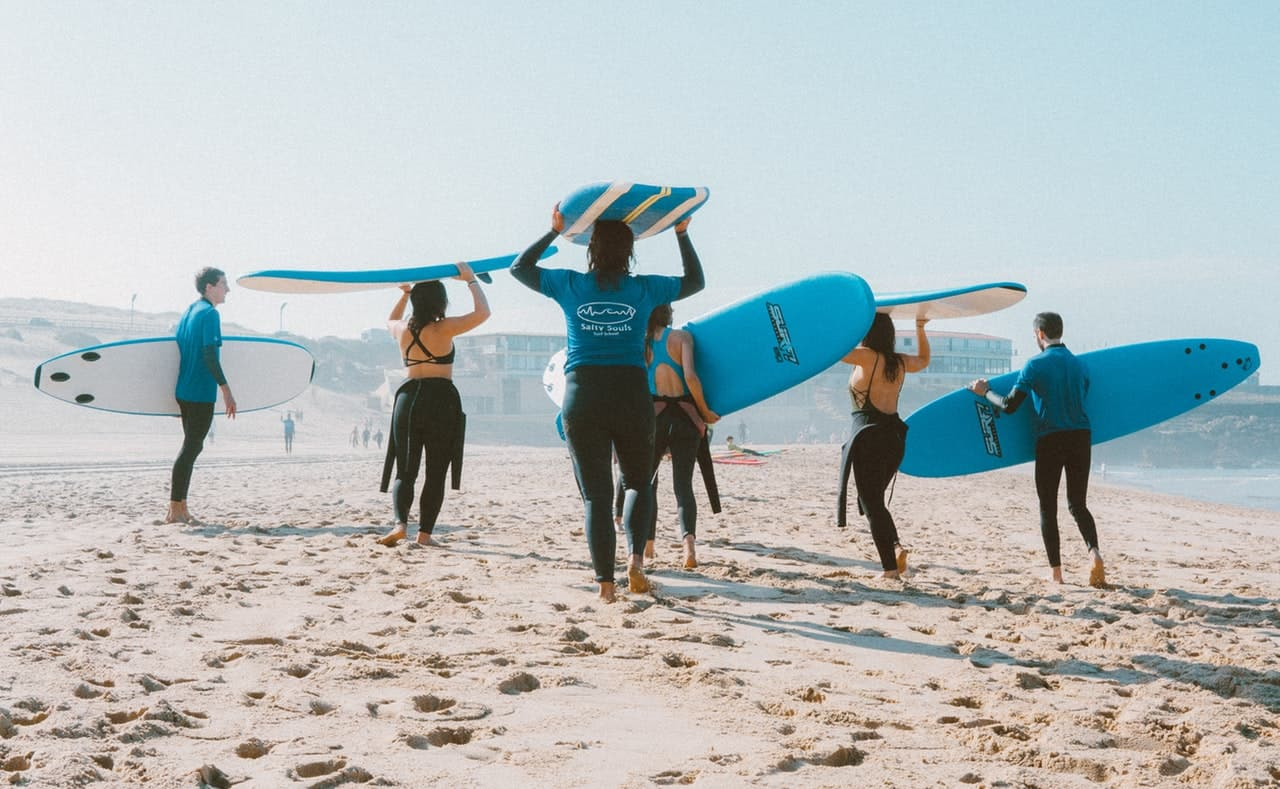 group of surfers carrying surf boards