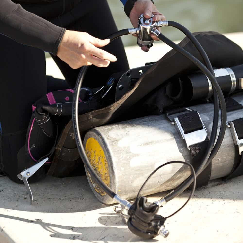 person assembling scuba gear