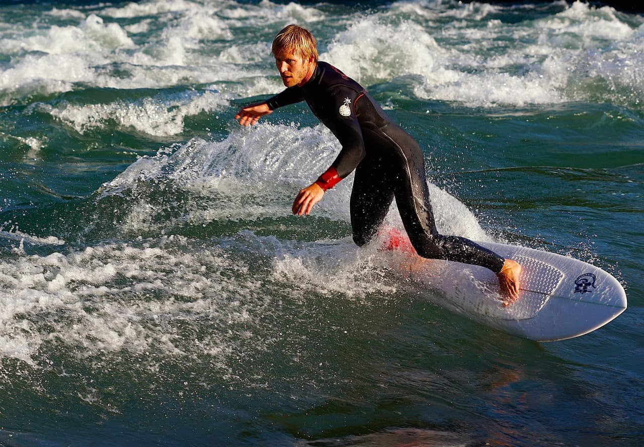 man on wetsuit surfing