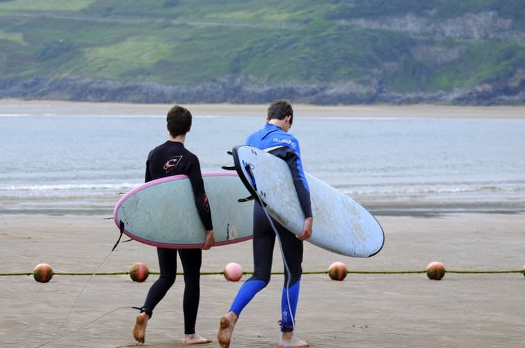 two men walking on the seashore carrying surfboards