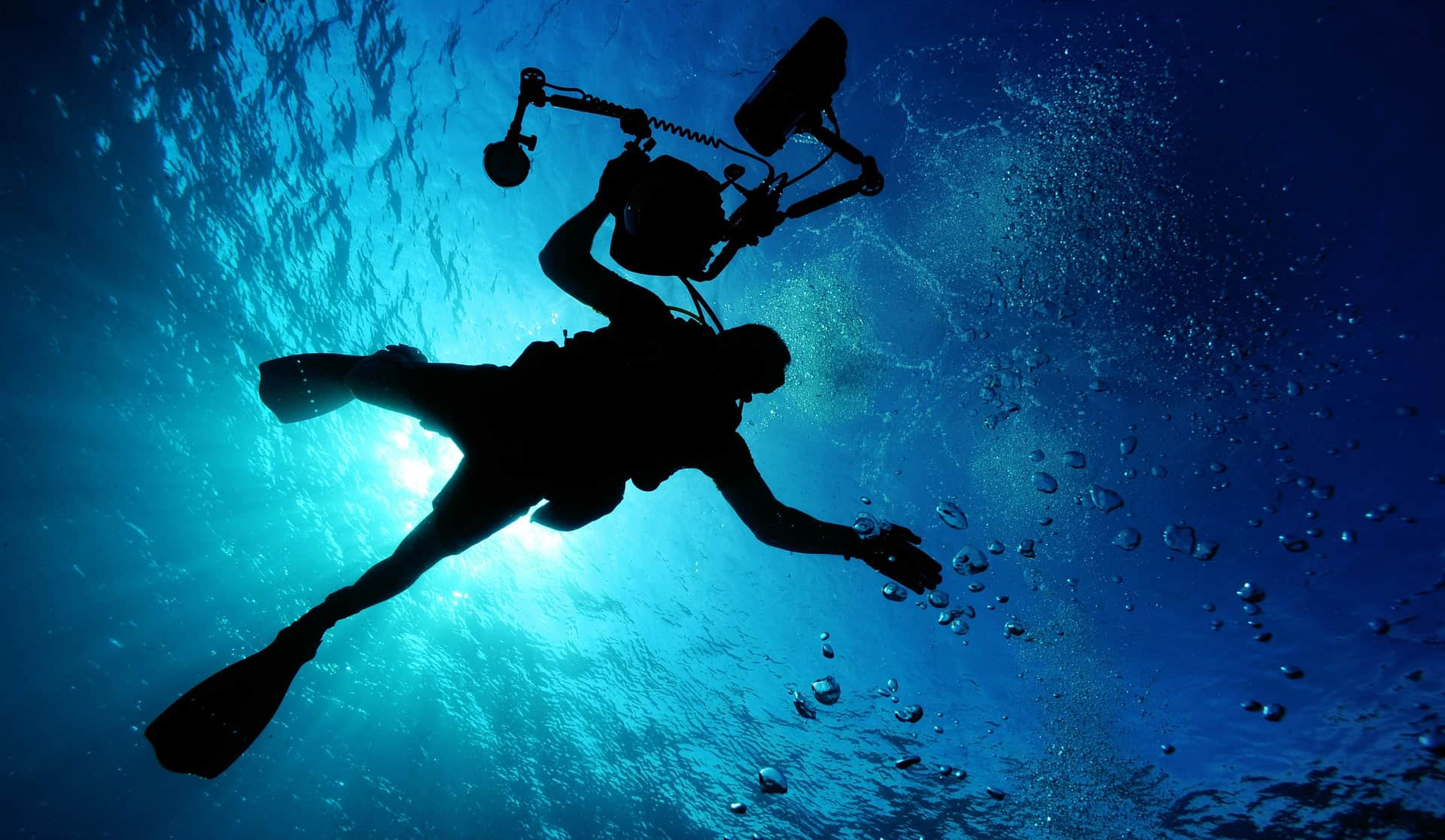 Diver holding a metal detector while swimming underwater