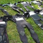 several wetsuits lying on lawn